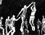 Terry Rand, Pat O'Keefe, and Rube Schulz defend against their opponents in a basketball game,...
