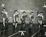 Marquette basketball players dribble basketballs while running toward the camera, 1941