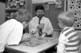 A professor plays a board game with two young boys, 1990