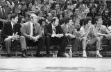 The men's basketball coaches, fans, and team watch the game from the sidelines, 1977-1978