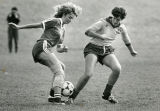 Female soccer players fight for the ball