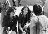 A small group of female students join in laughter while chatting outside, 1976