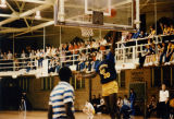 An unidentified basketball player goes up for a layup while a group gathers on the track in the...