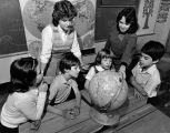 Marquette students instruct children in geography using a globe, 1984