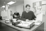 A Marquette student employee works at a desk, 1999