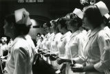 Nursing students hold candles at an unidentified service, 1972-1973