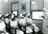 A nun lectures to a group of students in the College of Nursing