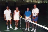 Participants in the Women's Council tennis tournament pose at the net for a picture