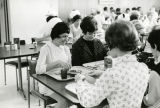 Nursing students finish eating a meal in a cafeteria