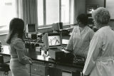 A student and two faculty members look at instructional media in the College of Nursing's lab