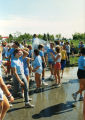 Runners cool off by walking through sprinkled water after Al's Run, 1986