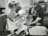 A student nurse and child play with a doll to reflect the child's treatment
