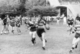 A player runs with the ball while closely followed by an opponent in a rugby game, 1971