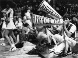 A male cheerleader yells into a megaphone, 1984-1985