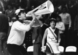 A male cheerleader yells into a megaphone at a basketball game while a female cheerleader also...