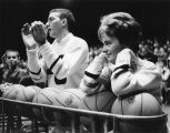 A male and female cheerleader lean on a rack of basketballs during a game, circa 1963