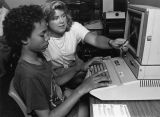 A female education student helps a girl using a computer in the Hartman Education Clinic, 1988