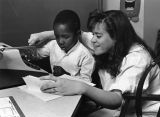 A female student works with a young boy at a typewriter in the Hartman Education Clinic, 1988