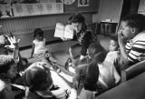 A faculty member of the College of Education reads to a group of young students, circa 1970