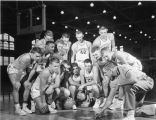 The Marquette men's basketball team watches as coach Jack Nagle shows them the plays, circa 1955