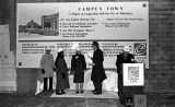 Dignitaries stand in front of a construction sign at the Campus Town Phase I groundbreaking, 1992