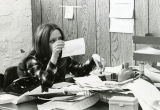 A member of the Tribune staff reviews some artwork at her desk, 1972-1973