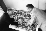 Roy Kallenberger and Sebastian Helfer examine an aerial photograph of campus, circa 1960