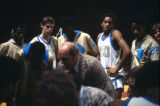 Players huddle around Rick Majerus for some basketball coaching, 1977-1978