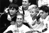 Members of the men's soccer team hug one another, 1986