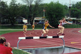 Brianna Dahm jumps a hurdle in the steeplechase, 2001