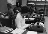 Graduate students work on stories at their typewriters, 1978