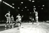 A Marquette basketball player attempts a long shot on the basket in a game against the University...
