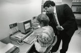 A College of Business Administration faculty member helps a student with her work at a computer...