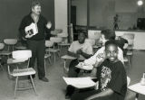 A member of the Instructional Media Center staff talks to a number of teenagers in a classroom in...