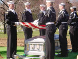 Sailors lower a flag of the United States over a casket containing the remains of Lieutenant Mike...