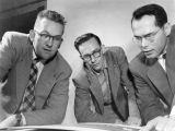 Clifford Helbert, Donald Ross, and Louis Belden inspect an advertising layout for a student...