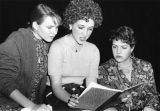A theater student reads from a composition book while two others look over her shoulder