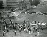 A crowd gathers around a makeshift stage for the groundbreaking of the Evan P. and Marion Halfaer...
