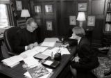 Robert A. Wild, S.J., and JoAnn Frederickson review paperwork at Wild's desk, 1996