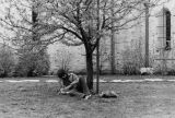 A student studies on the lawn outside the Saint Joan of Arc Chapel, 1974