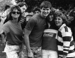 Four friends hug one another at a campus event, 1985