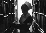 A nursing student consults a book in the library stacks, circa 1975