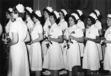 Nurses hold Nightingale lamps and roses for the Blessed Mother during capping ceremonies