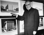 Edward J. O'Donnell, S.J. points to architectural drawings of buildings envisioned as part of the...
