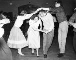 Sue Pfeil, Rosemary Spellacy, Pat Roe, and Jim Ehrhard dance the Virginia Reel, 1959-1960