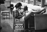 A student rests her feet on a desk while studying in the library, 1975-1976