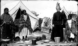 Woman in elk tooth dress, wth two sisters and Jesuit priest in camp near St. Francis Mission, 1914?