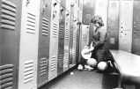 Unidentified athlete gets gear out of locker, 1983-1984