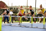 Megan Kosman and Joy (Krekelberg) Bauman jump hurdles against University of Wisconsin--Milwaukee...