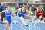 Joy (Krekelberg) Bauman (center) and unidentified track athlete jump hurdle, 1997